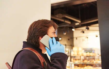 Man as a customer with face mask in the shopping mall is talking on the phone with the smartphone