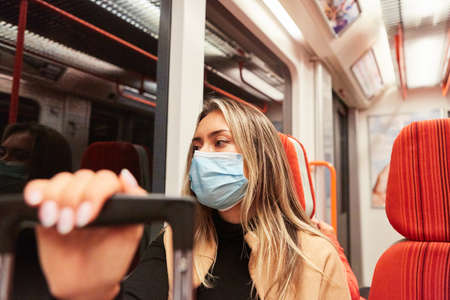 Commuter on bus and train in local transport with face mask because of Covid-19 pandemic