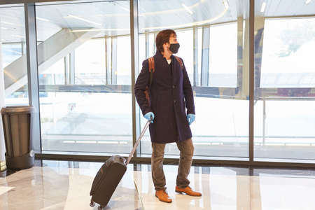 Business traveler with suitcase and face mask because of Covid-19 pandemic in the airport