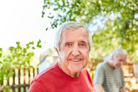 Sympathetic senior man as a pensioner in the garden in summer Stock Photo