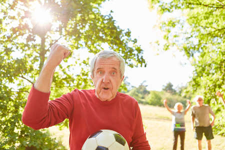 Senior as pensioner with soccer ball cheers with clenched fist after a soccer game