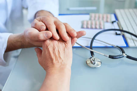 General practitioner holds the hand of a patient in both hands in the consultation hour