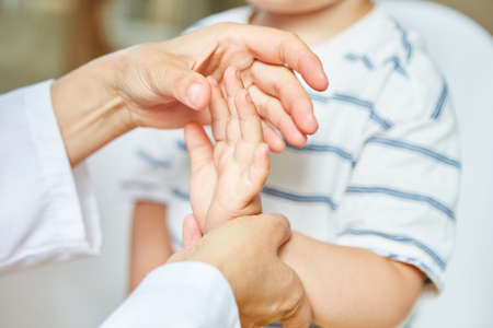 Chiropractor or osteopath treats hand of child with sprain on wrist