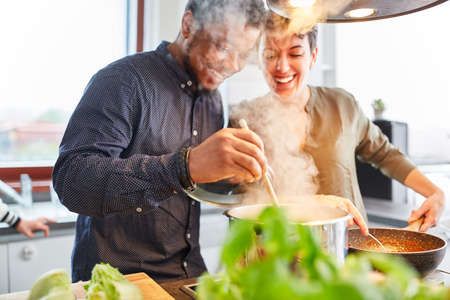 Happy friends or couple cooking food in kitchen for meal together