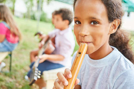 Girl learns to play the flute with friends in music class in summer camp course