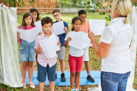 Children with music sheets sing together in a choir at holiday camp or summer camp