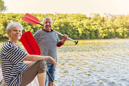 Happy senior couple with oars of row boat on lake in summer Banque d'images