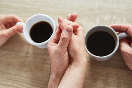 Two hands are touching while drinking coffee as a concept of comfort and affection