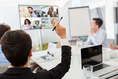 Business team in a meeting with video conference on a monitor