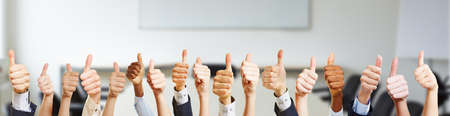 Many hands with thumbs up in the office Stock Photo