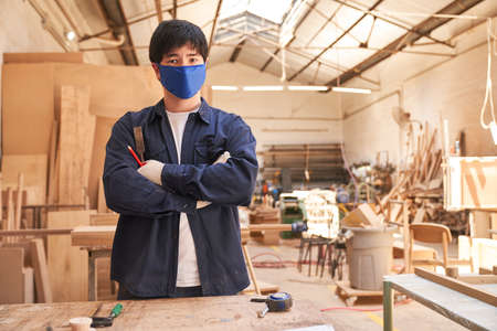 Young craftsman apprentice with face mask because of pandemic in the joinery Archivio Fotografico