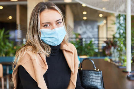 Woman with face mask because of pandemic sits in a cafe or restaurant