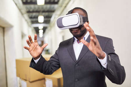 Entrepreneur in factory with VR glasses and virtual reality as future concept 版權商用圖片
