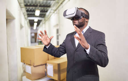 Entrepreneur with VR glasses has a virtual reality vision in the factory of the future