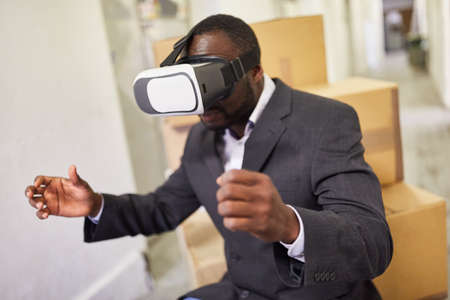Entrepreneur in a factory with VR glasses to simulate the virtual world of work 版權商用圖片