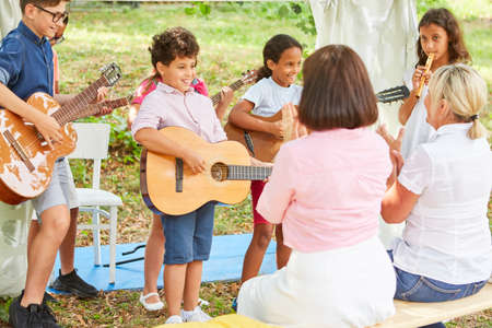 Children's group as a band at the talent show performance in front of an audience with guitars at the holiday camp