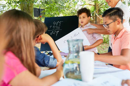 Group of children learns mathematics in tutoring lessons in summer school vacation course