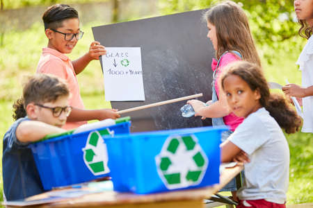 Children's group learns sustainability and environmental protection in a waste glass recycling campaign Foto de archivo