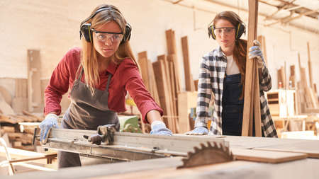 Two young women as carpenter apprentices work on the circular saw in the workshop