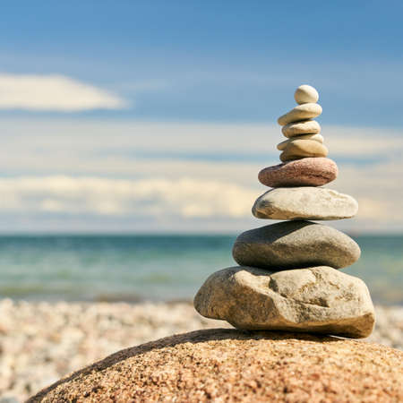 Zen meditation with stack of stones on the beach as a buddhism concept Stock fotó
