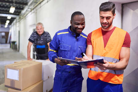Incoming warehouse clerk checks package delivery with checklist on clipboard
