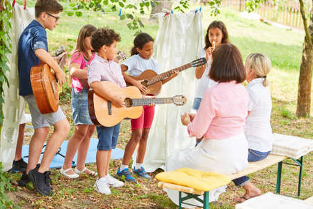 Group of children as a band with guitars at the talent show at the summer camp