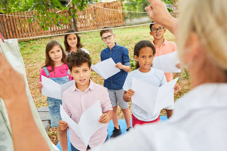 Children sing together in the choir in the summer camp under the guidance of the music teacher