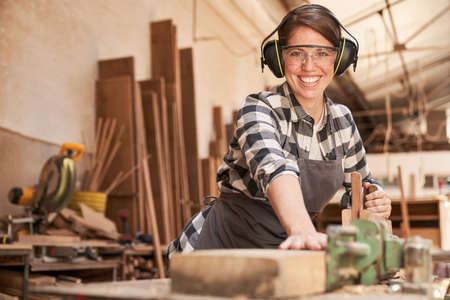 Happy young woman as a carpenter trainee at the planing machine of the joinery