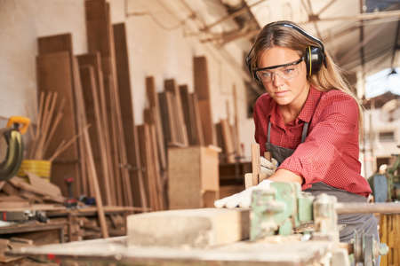 Woman as a carpenter trainee planing wood with a hand plane with hearing protection