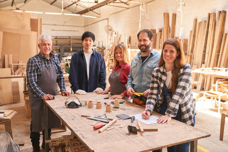 Group of craftsmen as a carpenter team in the carpentry workshop with apprentices
