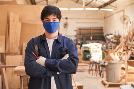 Apprentice carpenter with face mask because of in the carpentry workshop