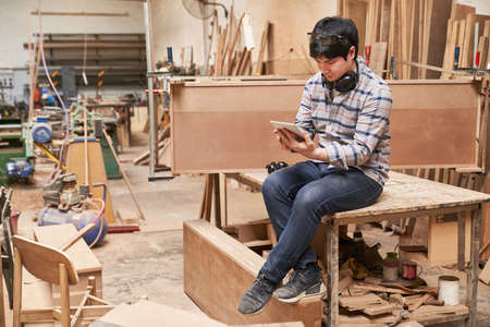 Craftsman trainee with tablet computer while chatting during a break in the carpentry shop