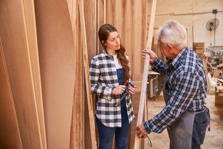 Senior craftsman as trainer with wife as carpenter apprentice measuring wood