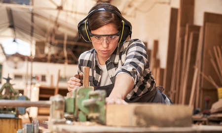 Young woman works as a carpenter or craftsman in a workshop with wood