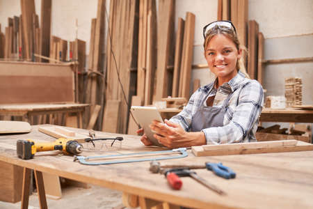 Young woman as a craftsman trainee with tablet computer in the carpentry workshop
