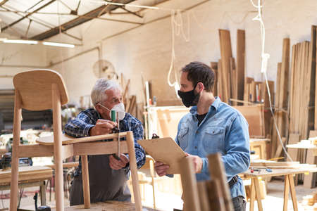 Senior craftsman and furniture maker apprentice with face mask because of Covid-19