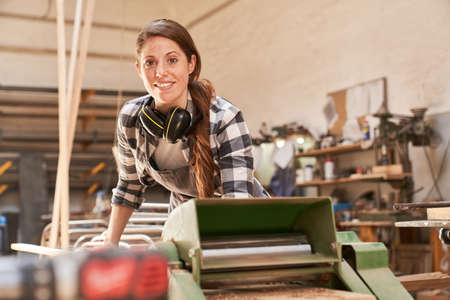 Woman as a craftsman trainee works on the thicknesser in the joinery