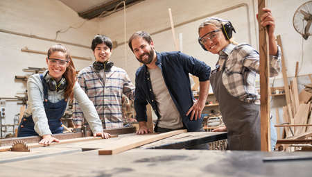 Group of craftsmen trainees and trainers at the circular saw in carpentry workshop