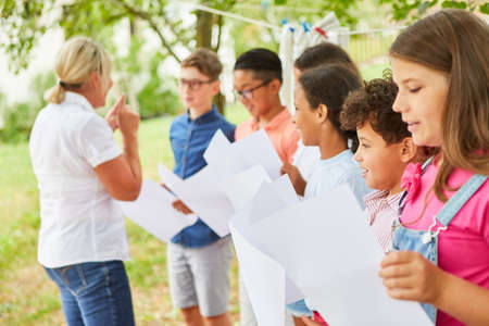 Teacher practices singing with the children's choir in the summer camp for the talent show