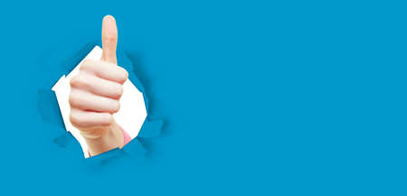Young woman showing thumbs up through hole in blue paper as success concept
