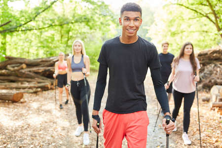 Young people as friends in a Nordic walking group in nature in summer 免版税图像