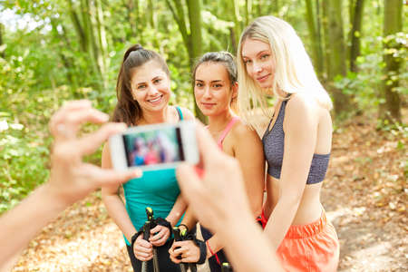 Three sporty women as friends are photographed while Nordic walking
