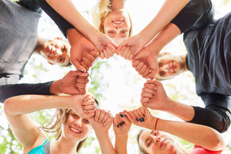 Group of teenagers standing in a circle with clenched fists for team building and motivation