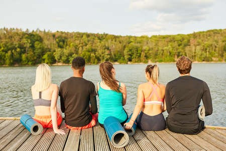 Young people as friends sit relaxed in nature at the lake after a fitness class