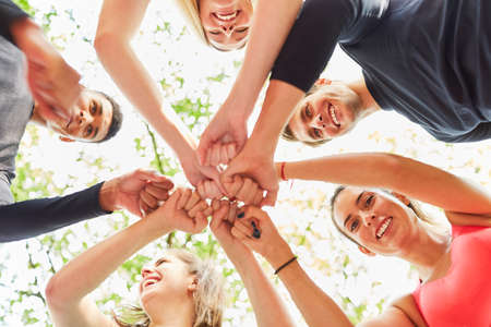 Group of friends greet each other with their fists as team building in nature