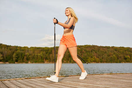 Sporty young woman while Nordic walking trains her endurance in nature at the lake