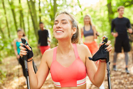 Happy young woman exercising with nordic walking group in nature in summer