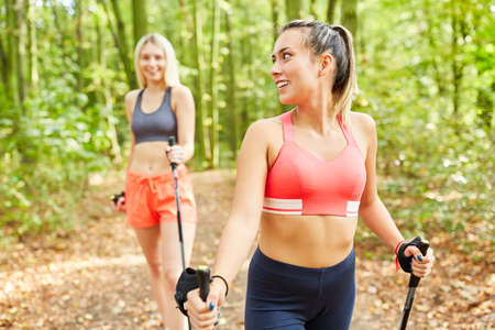 Two young women train together for endurance with Nordic Walking