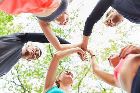 Young people give high five in nature for team building and cooperation