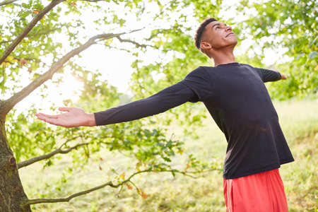 Young man with arms outstretched doing breathing exercise for health and stress relief